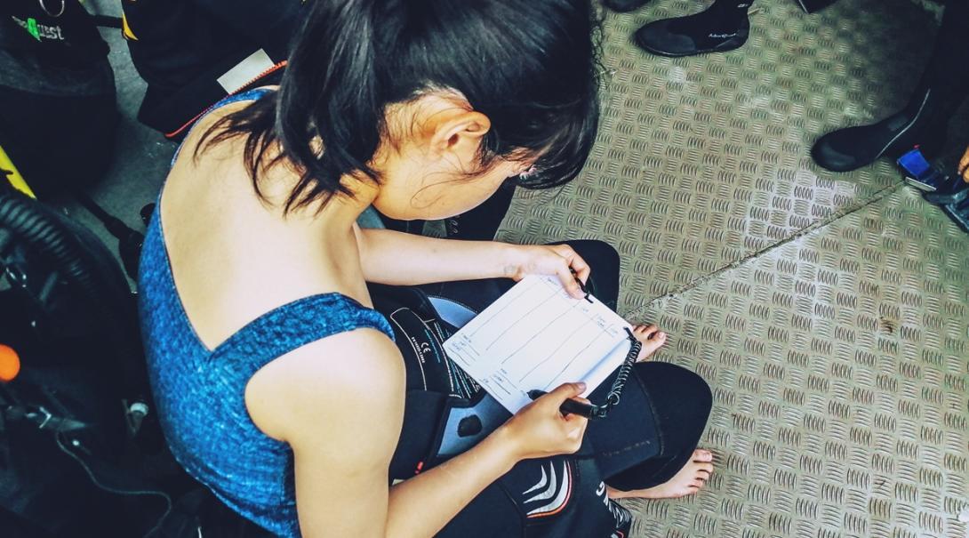ダイビング調査前にメモをとる日本人高校生環境保護ボランティア